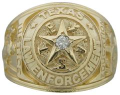 One of our class ring style law enforcement ring designs.  #1586-56 is shown in 14k yellow gold with a 0.08 ct. round brilliant diamond center.  This design is available with or without a center stone and in any color or karat of gold.